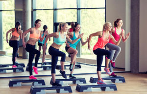 35027127 - fitness, sport, training, gym and lifestyle concept - group of women working out with steppers in gym